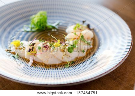 Raw scallops sashimi seafood dish. Fresh raw scallops sashimi dish. Sashimi is a Japanese cuisine delicacy consisting of sliced raw meat (usually fish and seafood) often served in sushi restaurants.