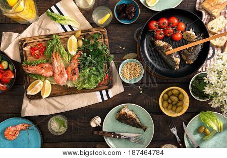Dinner table with shrimp fish grilled salad different snacks and homemade lemonade top view