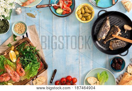 Frame of shrimp fish grilled salad and different snacks on a blue rustic wooden table top view. Family dinner table concept