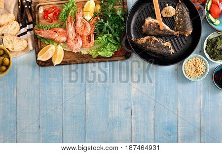 Family dinner table with shrimp fish grilled salad different snacks with border top view