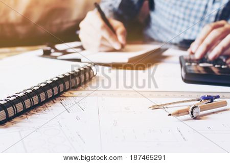Architect engineer man calculate building area with equipment on desk.