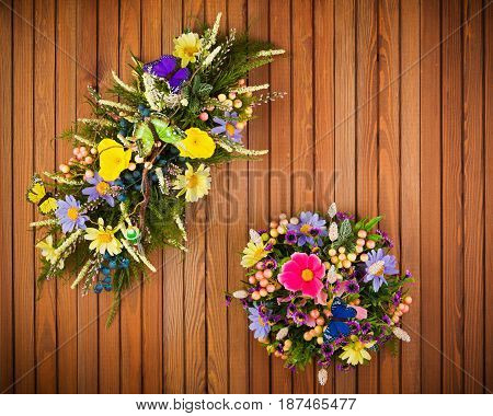 Colorful composition made of artificial flowers, fruits, butterflies and ears of wheat in stylish vase on white wooden background.