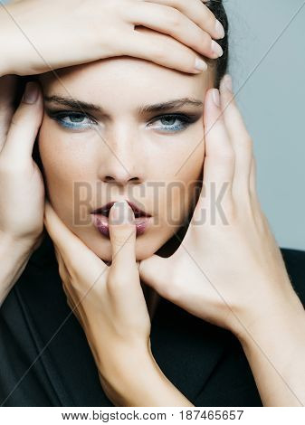 Many hands touching pretty face with freckles of girl with young healthy skin fashionable makeup sexy lips on grey background. Beauty and skincare