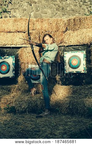 young archer girl with bow near hay with target sunny outdoor summer activity