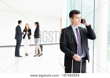 Traveling businessman calling on smartphone at building hallway (airport terminal)