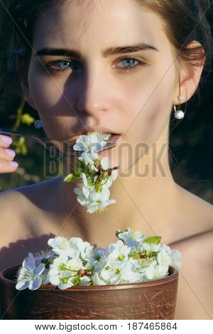 dieting. woman with blue eyes on young face eating cherry blossom petals white flowers with metallic fork on natural background. Healthy dieting