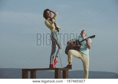 Woman Singing On Table And Handsome Man Playing Guitar