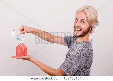 Household savings and finances economy concept. Smiling man putting zlotych money into a piggy bank in the shape of a house studio shot on grey background