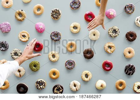 Hands selecting a variety of donut flavor