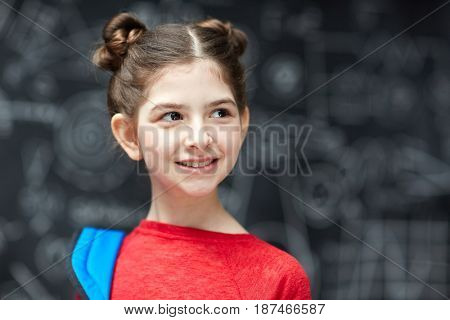 Portrait of cute little girl with dark hair smiling looking away posing against blackboard ready to go to school