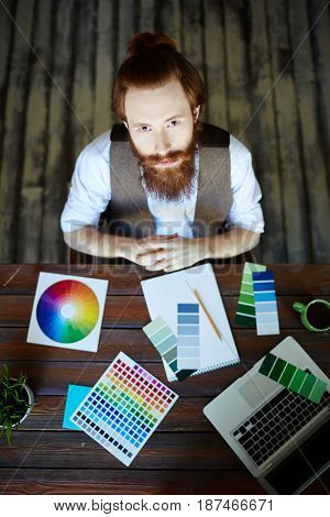 Directly above view portrait of creative bearded man looking up at camera while working in modern design studio, choosing color scheme from swatches