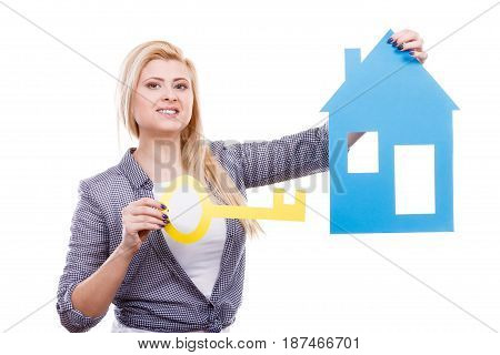 Dream about stabilization plans for future. Blonde girl holding blue paper house model and yellow key cutout. New flat apartment. Isolated on white