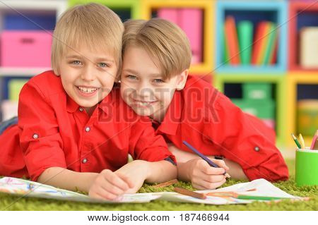 Portrait of two cute brothers draws with pencils