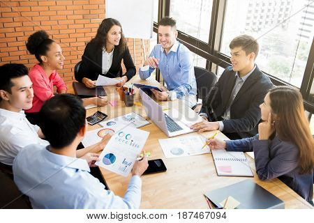 Group of mixed race business people having a meeting in casual office - teamwork and brainstorming concepts