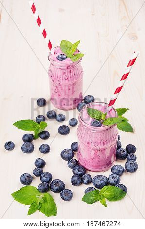 Violet blueberry fruit smoothie in glass jars with straw mint leaves berries close up. White wooden board background.