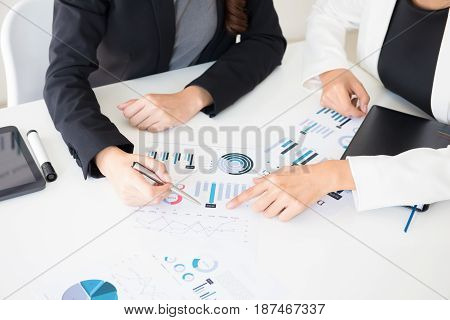 Businesswomen discussing and analyzing financial graph documents