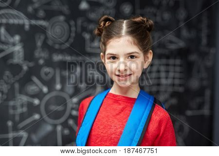 Portrait of cute little girl with dark hair smiling and looking at camera posing against blackboard ready to go to school