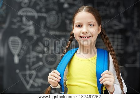 Portrait of happy little girl with two braids posing against blackboard ready to go to first day of school
