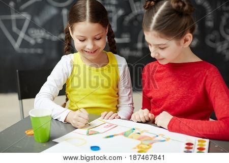 Portrait of two smiling little girls painting pictures together in art studio class sitting against blackboard