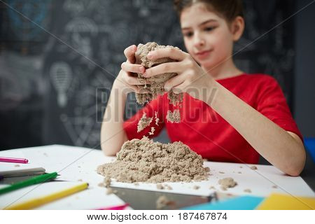 Portrait of little girl playing with kinetic sand during art class in child development center