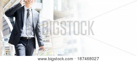 Businessman calling on cell phone while pulling baggage and walking in outdoor covered walkway panoramic banner with copy space