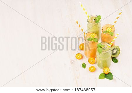 Freshly blended orange kumquat and green kiwi fruit smoothie in glass jars with straw mint leaf cut ripe berry copy space. White wooden board background.