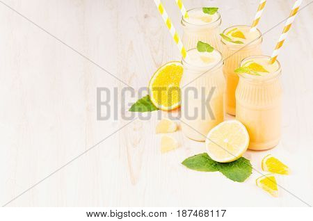 Freshly blended orange and yellow lemon smoothie in glass jars with straw mint leaf copy space. White wooden board background.