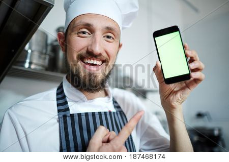 Bearded baker pointing at smartphone in his hand