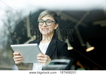 Portrait of young woman with creative haircut and glassed, gen Y representative, using digital tablet for  work in office and smiling to camera