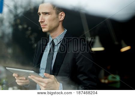 Portrait of young handsome businessman using digital tablet for  work in office looking away pensively, standing by window