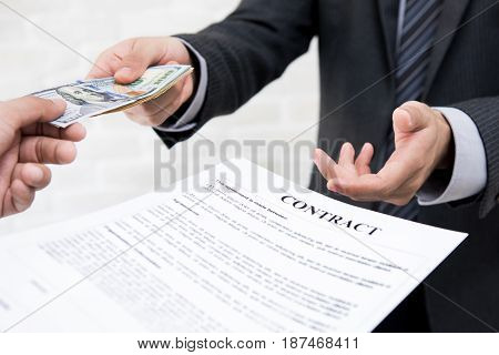 Businessman giving money together with contract - debt loan and bribery concepts