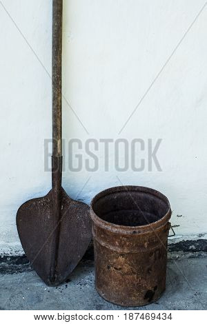 a Rusty shovel and bucket on a white background