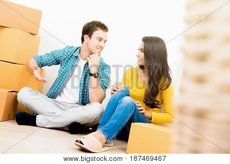 Interracial couple sitting on the floor and talking after moving into new house