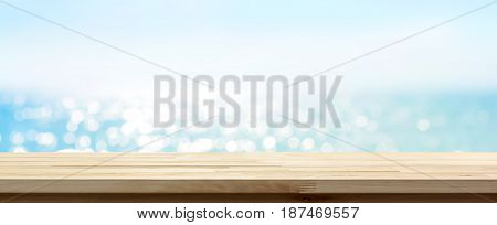 Wood table top on blue summer sparking sea water bokeh banner background - can be used for display or montage your products