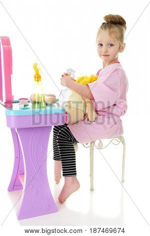 An adorable preschooler contentedly sitting at her hairdressing station with a doll and spray bottle on her lap.  On a white background