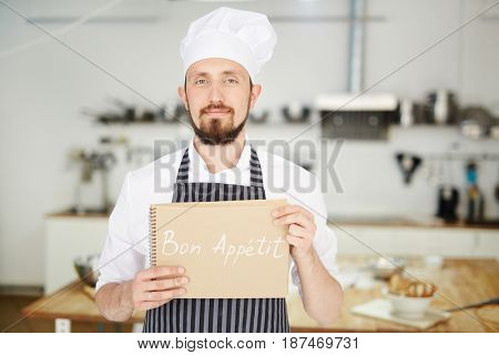 Professional baker holding notepad with wish of good appetite
