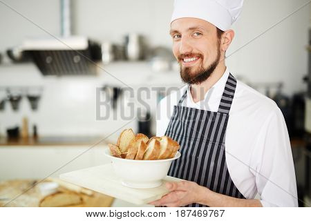 Chef of pastry serving crusty slices of bread