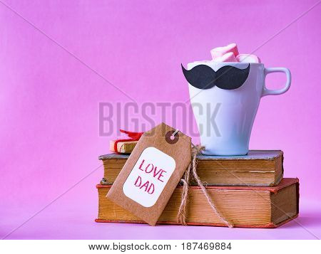 Father's day concept. LOVE DAD alphabet on stack of books gifts tea cup with black Mustache on pink background