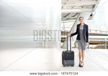 Young Asian businesswoman walking at outdoor covered walkway with baggage - business travel concept