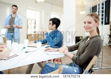 Pretty young designer making notes in notepad in working environment