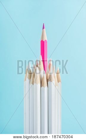 Business concept - lot of white pencils and one color pencil stand on blue paper background. It's symbol of leadership teamwork united and communication.