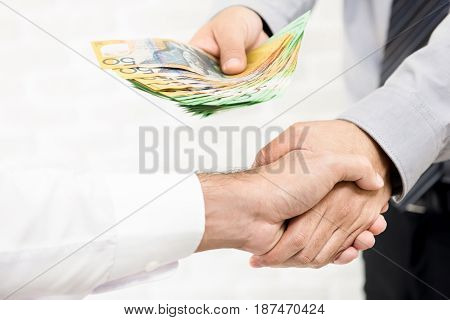 Businessman giving money Australian dollar bills while making handshake