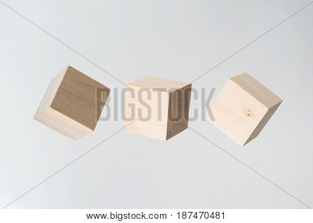 Business concept - Abstract geometric real floating wooden cube on grey background and it's not 3D render.