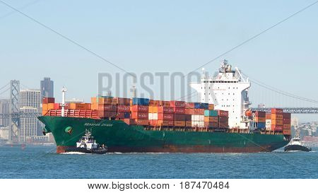 San Francisco CA - May 21 2017: Cargo ship SEASPAN CHINAN manuevering through the bay in route to the Port of Oakland the fifth busiest port in the United States.