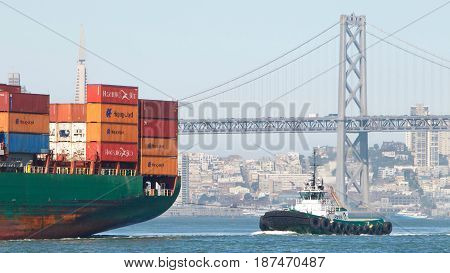 San Francisco CA - May 21 2017: Foss tugboat LYNN MARIE at the stern of cargo ship SEASPAN CHIWAN assisting the vessel to maneuver into the Port of Oakland.