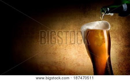 Beer pouring into glass on a textured background
