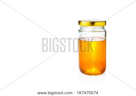 golden honey in glass jar with lid on isolated white background room for copy space