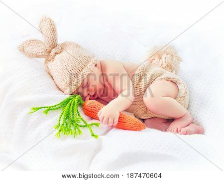 Very cute Two weeks old smiling newborn baby boy wearing knitted bunny costume, hat with rabbit ears, tail and funny carrot toy. Sweet new born baby portrait sleeping in his bed.