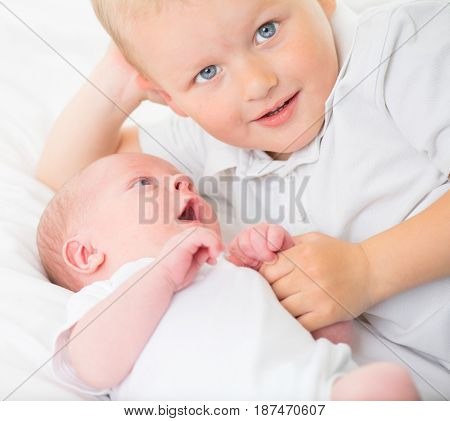 Newborn baby with older brother playing together. Little brothers of two years and two weeks old together. Happy and healthy family portrait.