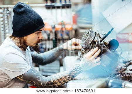 Young man with tattoos repairing bike engine